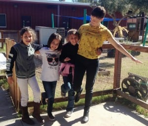 Emily and three students giggle and hold each other up while balancing on one foot.