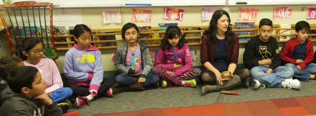 Neena Barreto sits with her students.